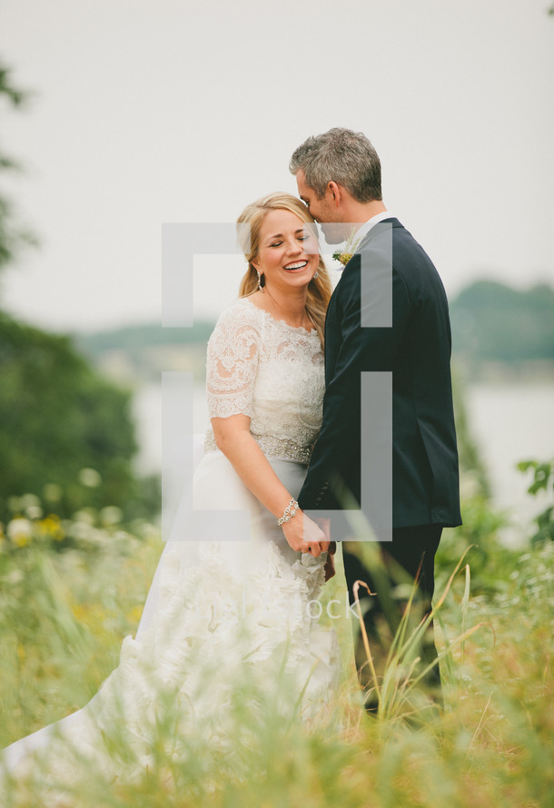 Married couple standing in field
