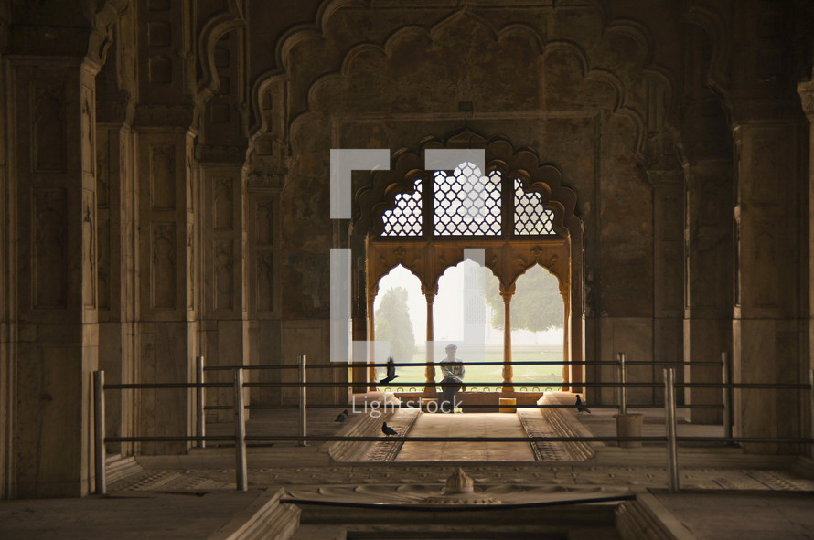 man sitting in the window of a palace mosque