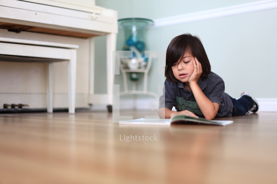 Boy reading book on bedroom floor
