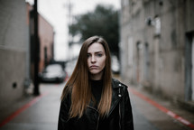 a young woman standing on a city street facing the camera with sad eyes