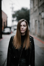 a woman in a leather jacket standing on a narrow city street