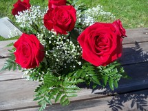 A fresh bouqet of red roses blooms in the sun surrounded by babies breathe and green leaves waiting to be given as a gift for a loved one on Valentines day, wedding day or anniversary.