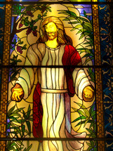 A gold, yellow, rose colored, red and brown Stained glass window of Jesus Christ, the son of God in a long white and red robe with his nail scarred hands stretched out and smiling peacefully showing grace, mercy and love to all who view this image.