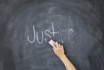 erasing the word Justice off a chalkboard