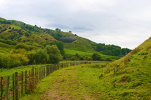 fence line and green hills
