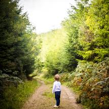 a toddler boy standing on a dirt path