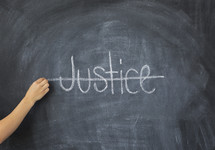 crossing through the word Justice on a chalkboard