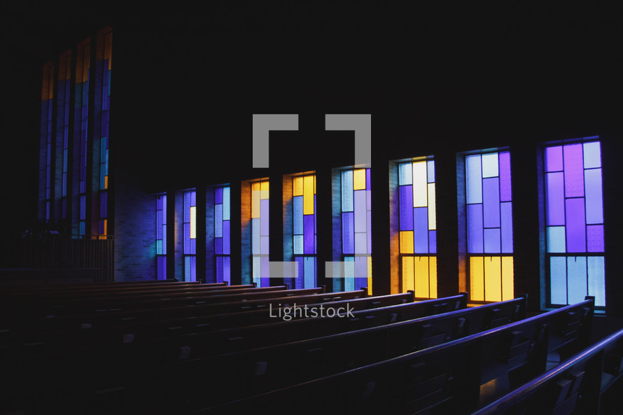stained glass windows in a church and pews