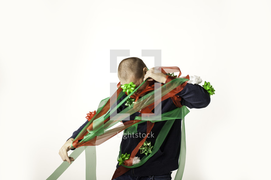 Christmas consumerism - man wrapped up and trapped in Christmas ribbon