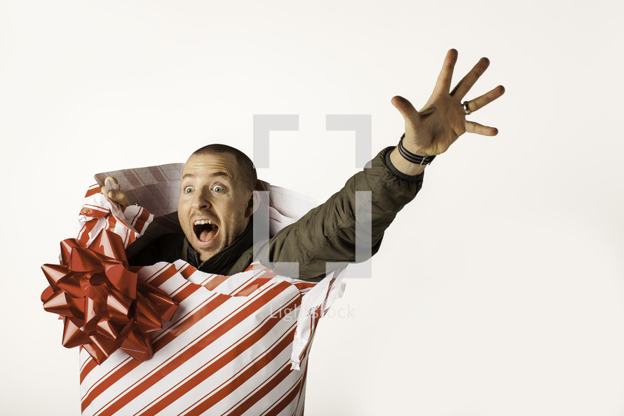 Christmas consumerism - man wrapped up in Christmas paper reaching out for help