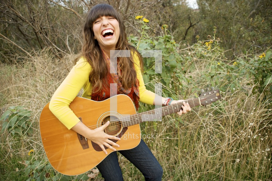 woman laughing playing a guitar