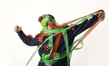 Man tangled in red and green ribbon with bowc stuck to his body and head.