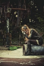 woman in despair sitting on a pipe with her head down
