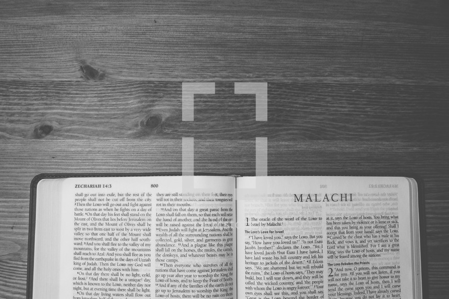 Bible on a wooden table open to the book of Malachi.