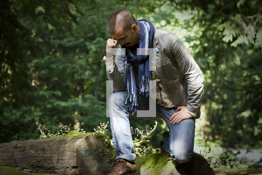 Tebowing:  man crouched or kneeling on logs with his fist to his forehead in a forest.
