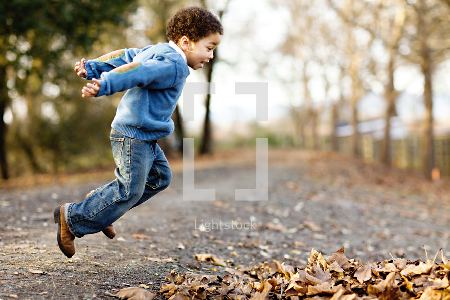 Boy jumping into leaves fall autumn road