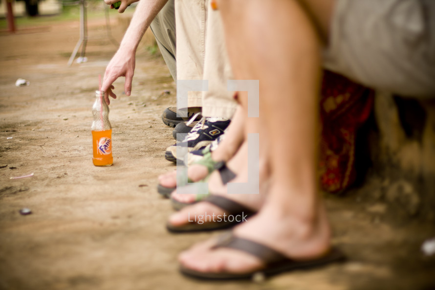 A row of legs and feet - A hand reaches for a drink