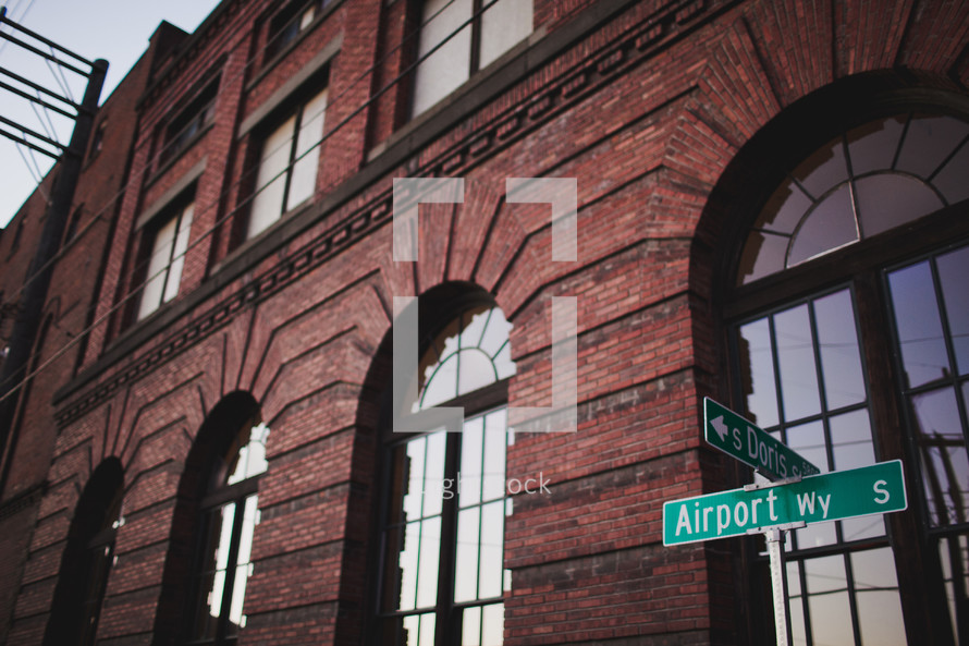 street signs in front of a brick warehouse building