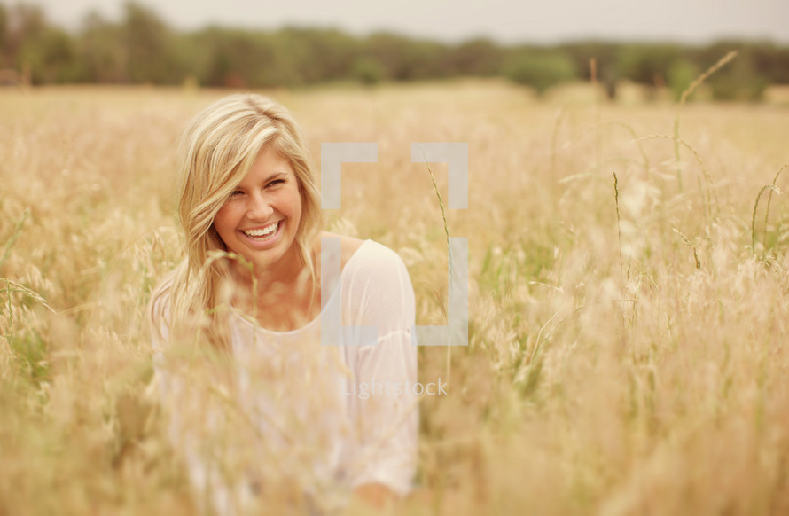 smiling woman in the tall grass in a field