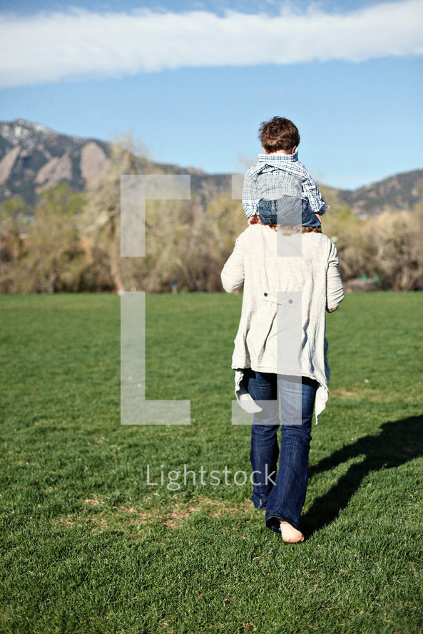 mother walking in the grass with toddler son on her shoulders