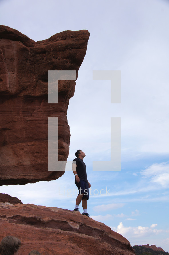 man standing on red rock looking upward