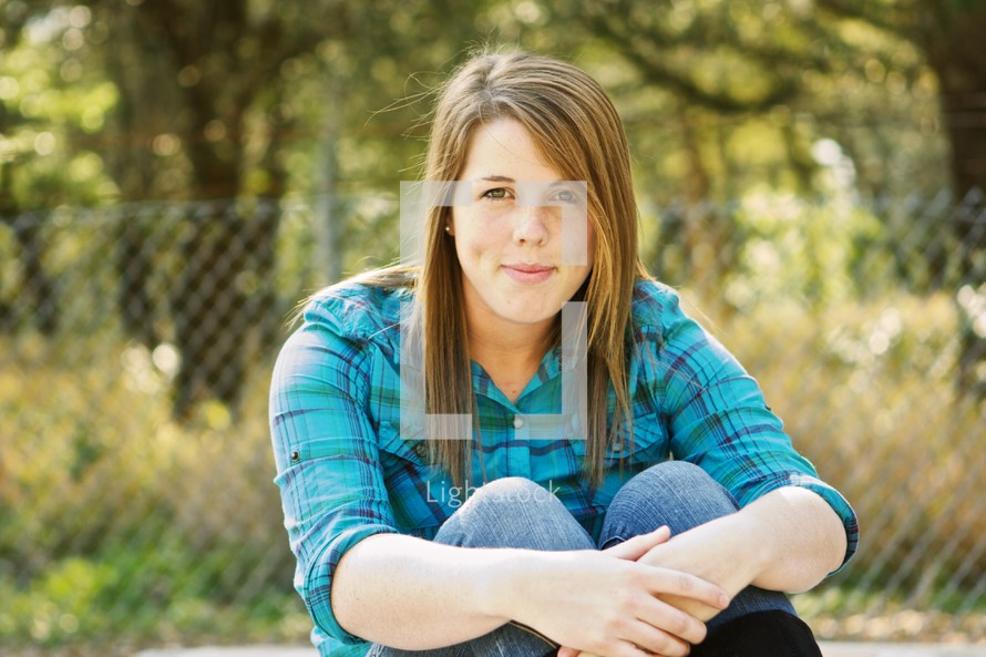 Woman sitting in front of fence