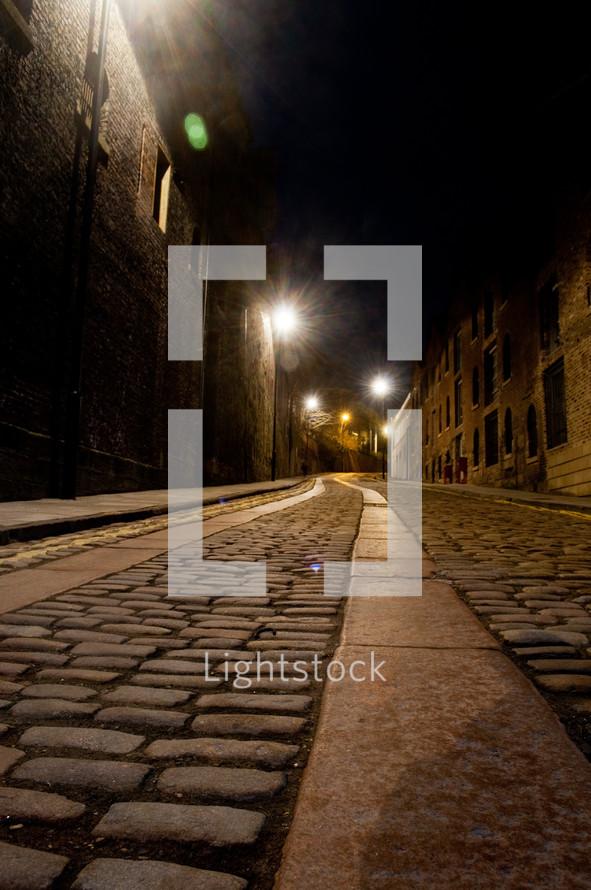 Cobblestone walkway in between brick buildings with beaming street lights in background.