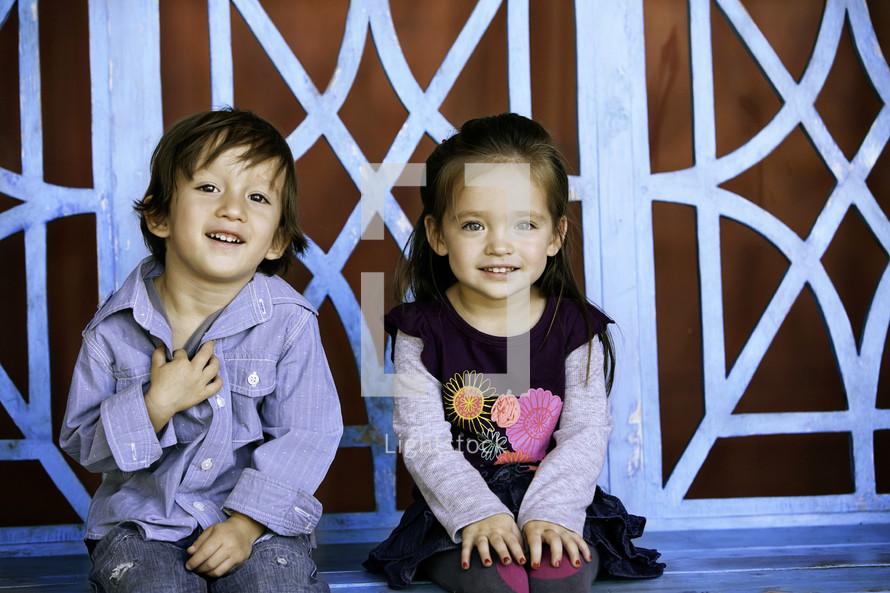 A little boy and girl sitting and smiling