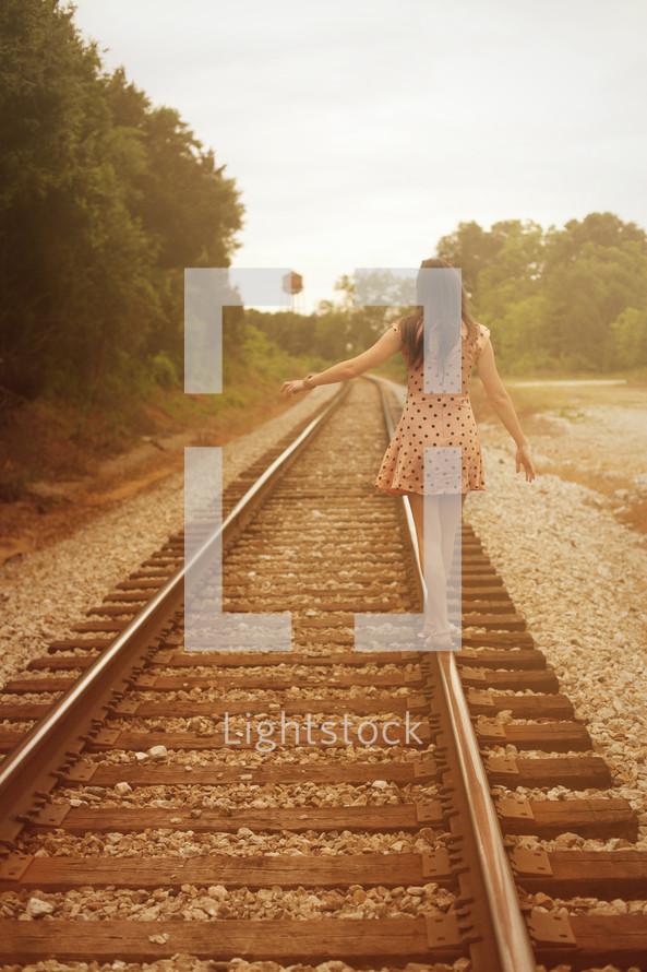woman walking down railroad tracks