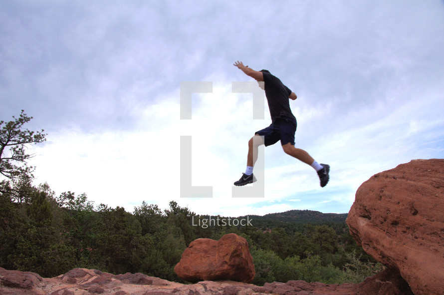 man jumping from a rock ledge