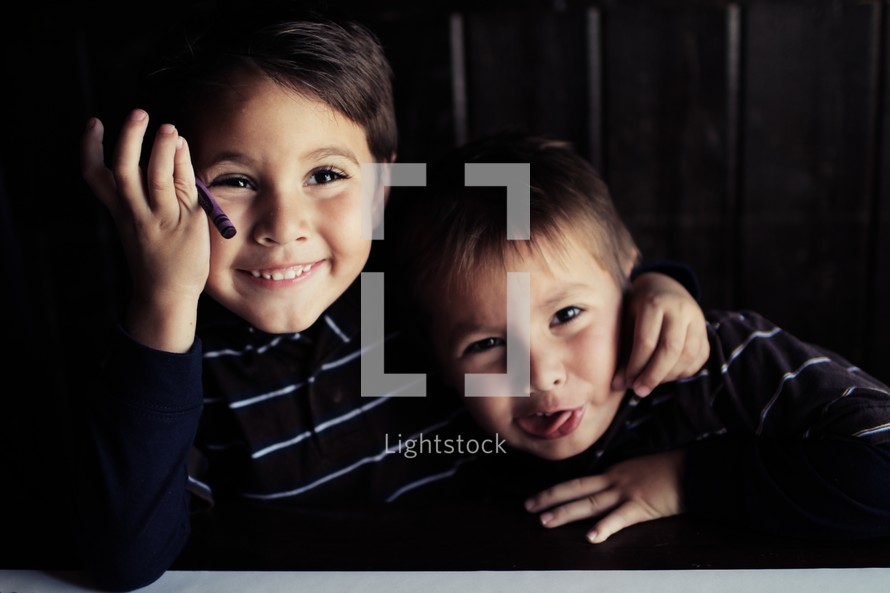 Two brothers hugging and coloring