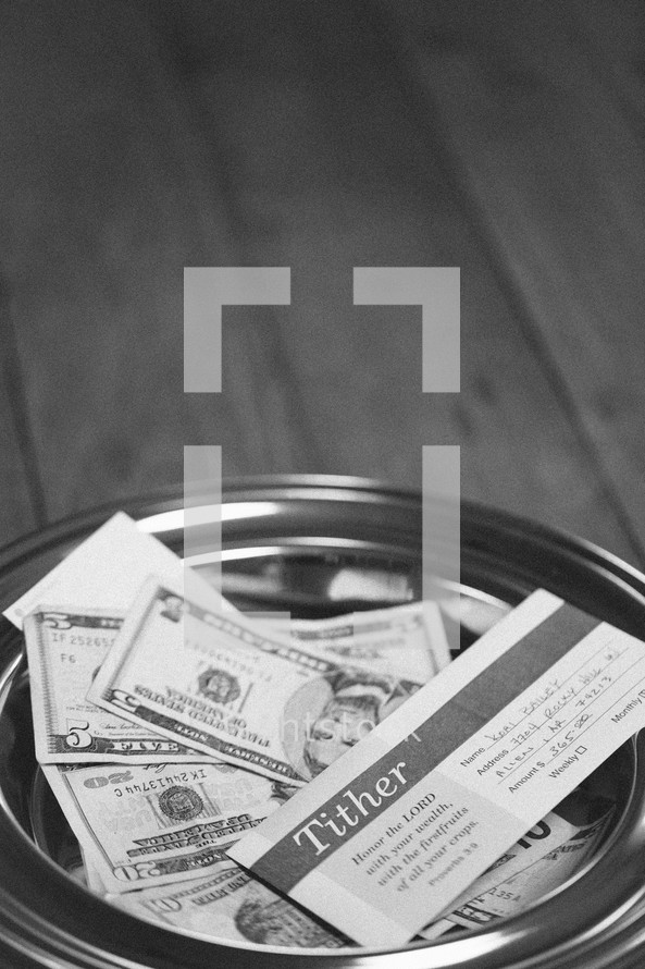 cash and envelopes in an offering plate