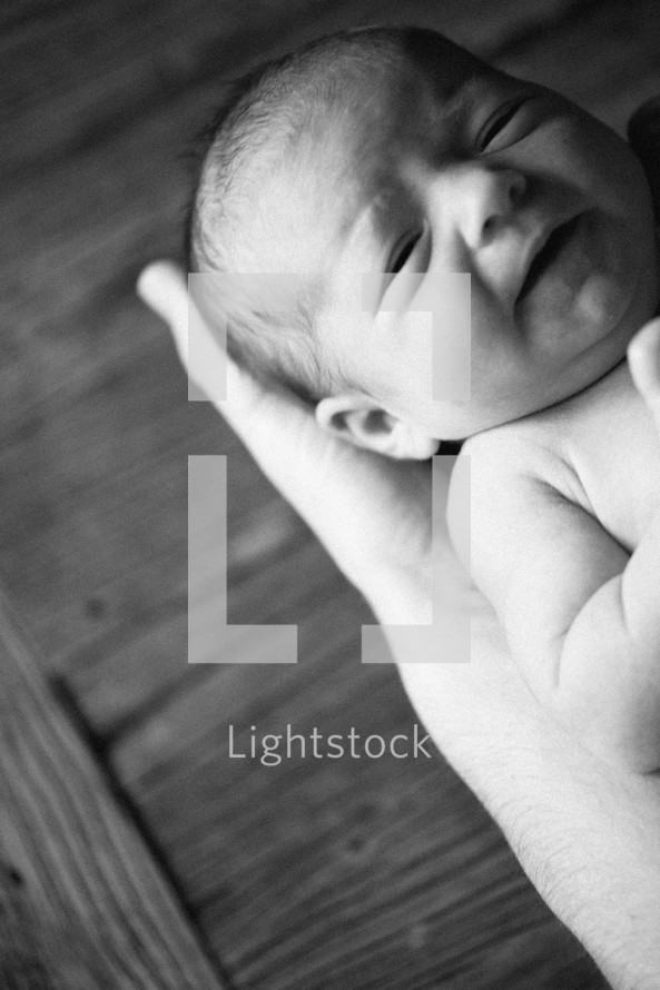 A baby held in his Father's hands