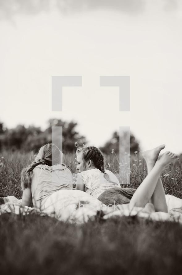 Two girls lying on a blanket in a field.