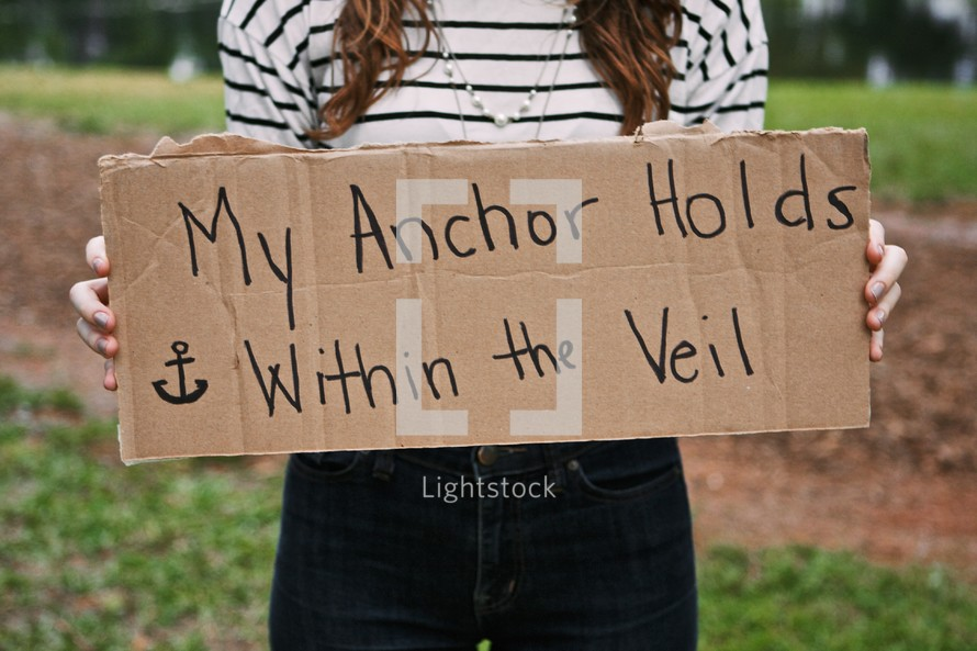 Woman holding a sign with the words MY ANCHOR HOLDS WITHIN THE VEIL