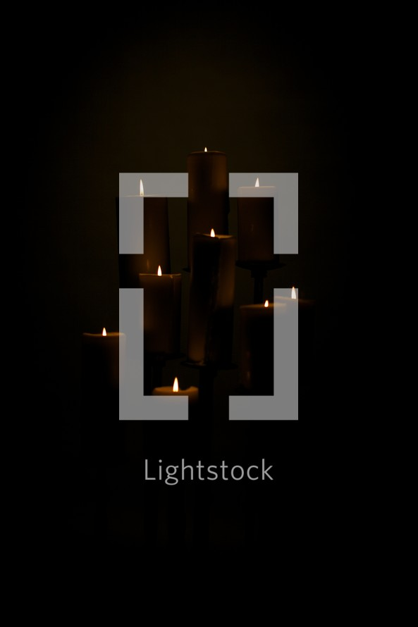 A group of candles lit in a dark room - isolated on black