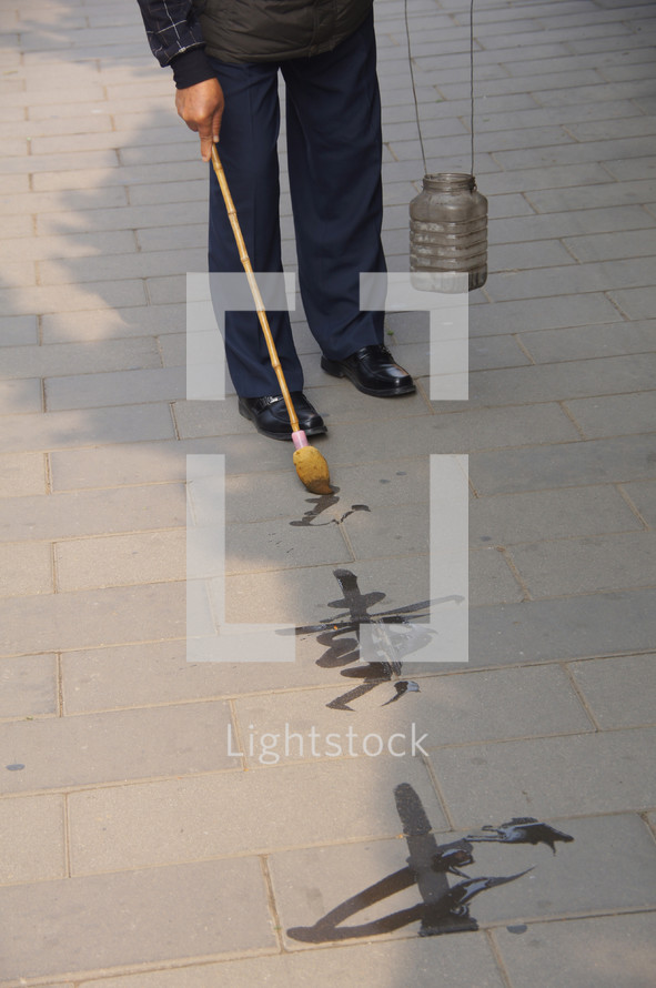 Old man painting Chinese symbols on a sidewalk with water