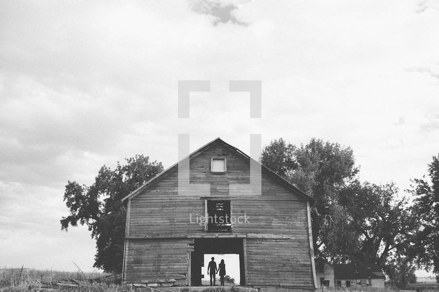 Couple standing in abandoned barnhouse