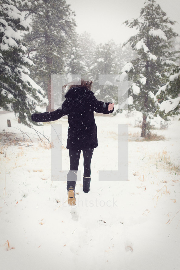 Woman running in a field of winter snow