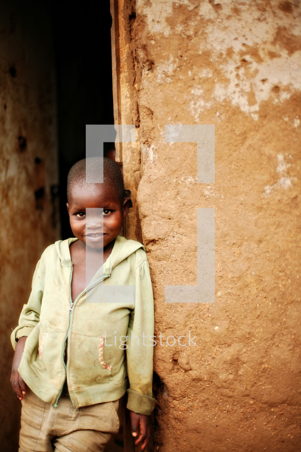 A young boy leaning against a wall