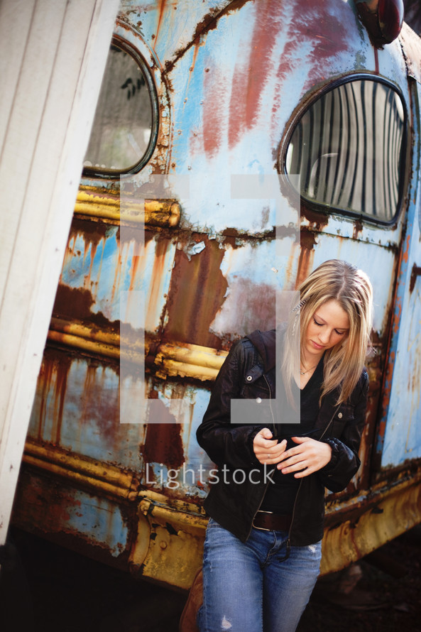 woman standing in front of an old bus looking down at her hands
