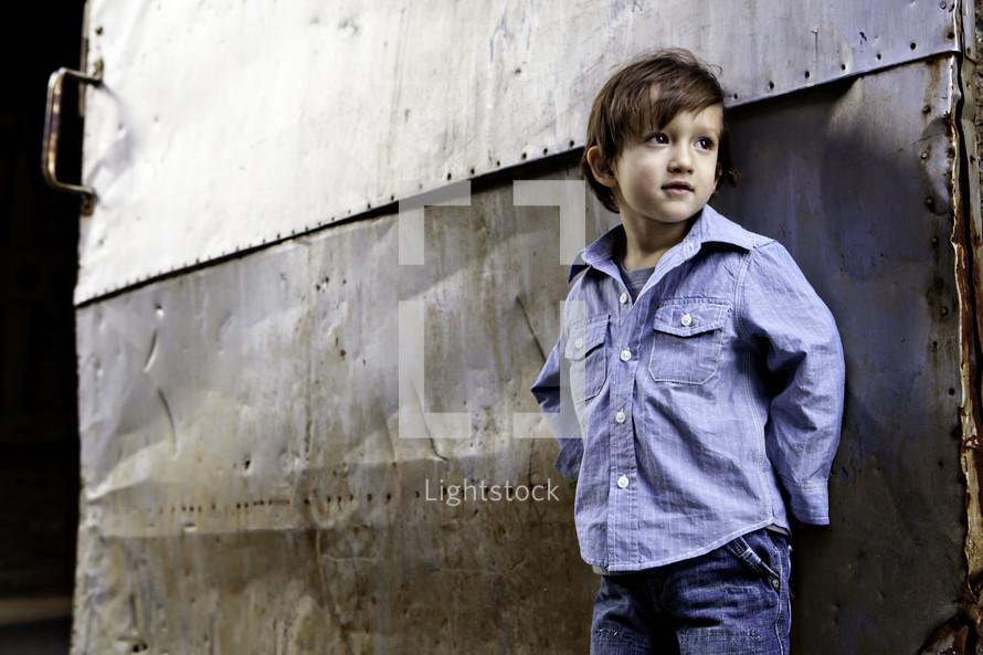 boy standing against metal door -  looking away