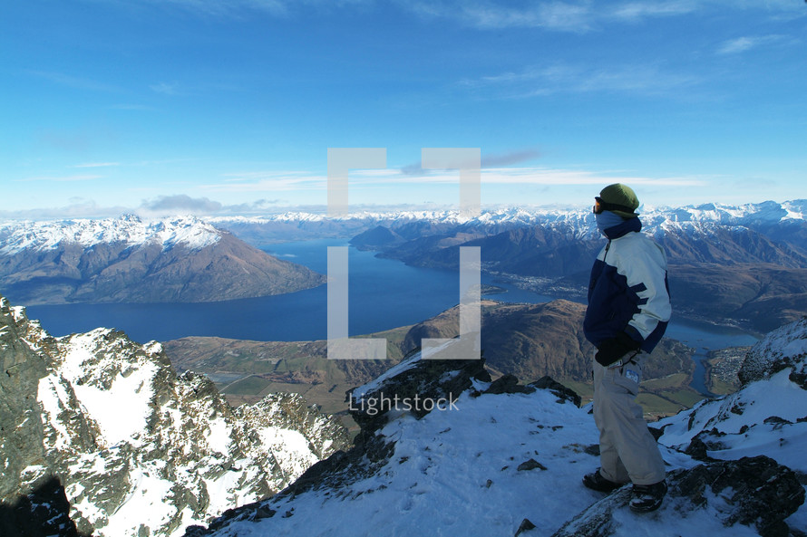 Man standing on snow-covered mountaintop overlooking a river