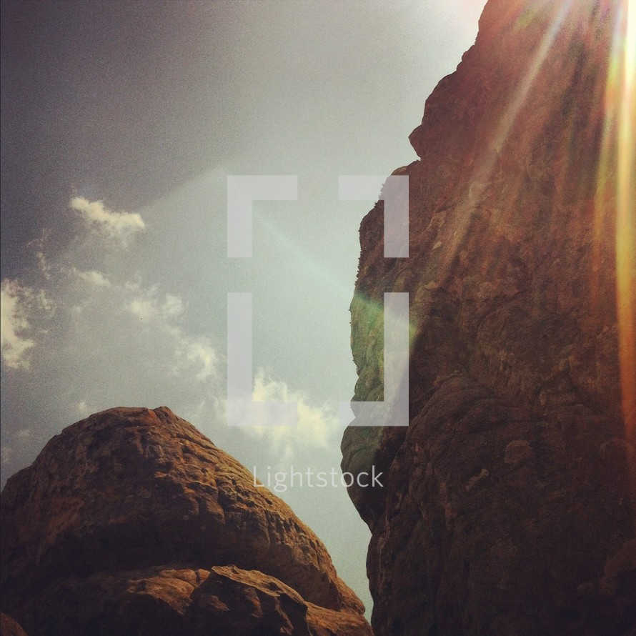 rays of sunlight on a rock peak