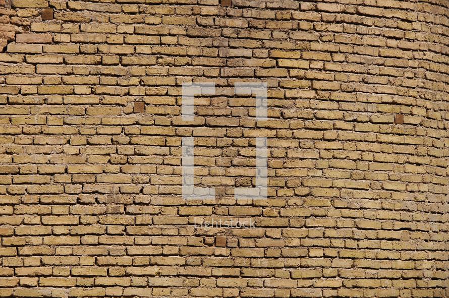 Tan brick wall made from hand made bricks