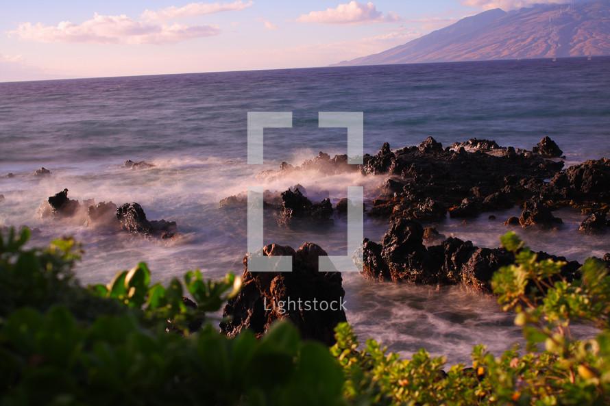 ocean water crashing into volcanic rock