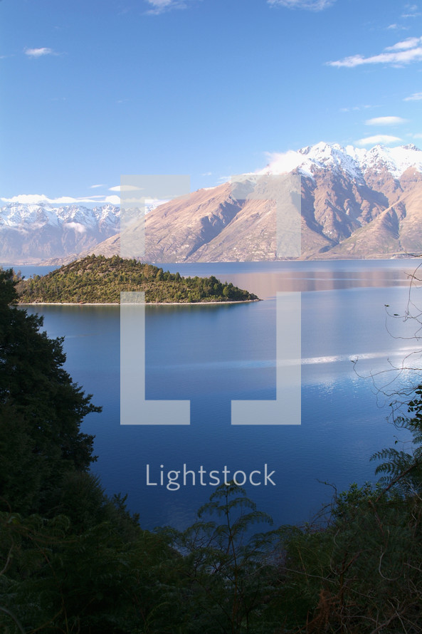 lake with island and snow capped mountain range