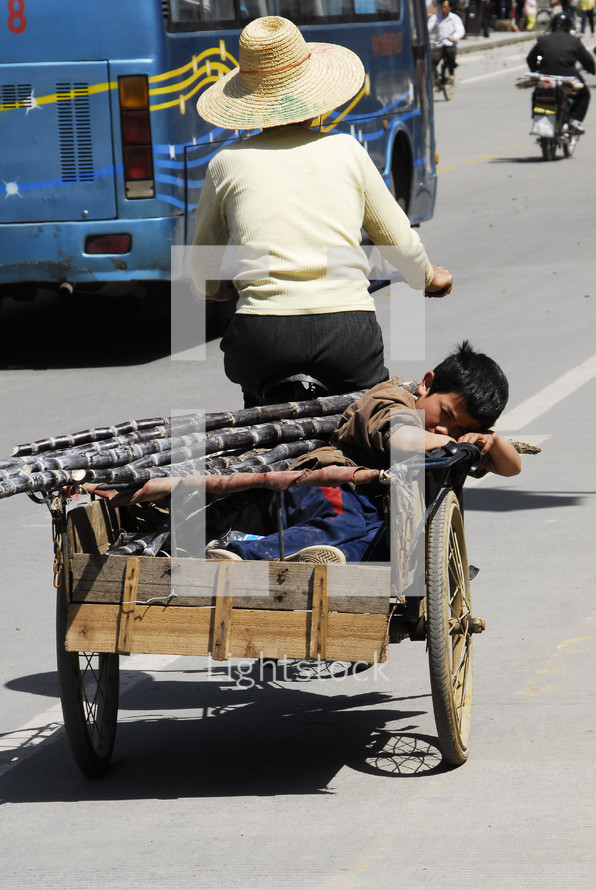 Woman - bicycle pulling wagon with boy asleep - street - Asian