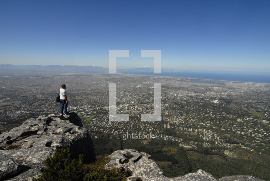 Man on mountain top looking out over a city by the sea