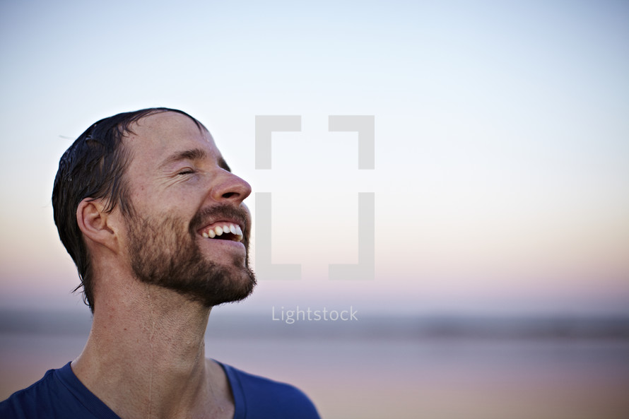 Smiling man with eyes closed with face towards the sky.